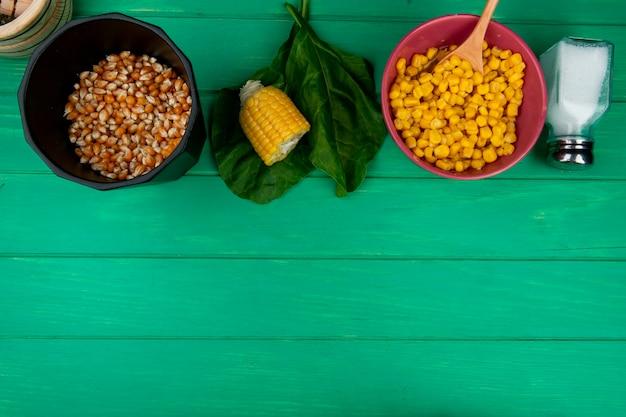 コピースペースを持つ緑の表面にカットコーンソルトとほうれん草のトウモロコシ種子のトップビュー