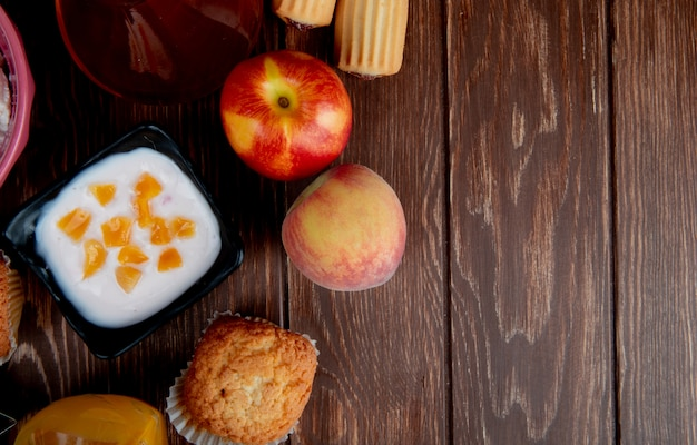 コピースペースを持つ木製の表面に桃のカップケーキとカッテージチーズのトップビュー