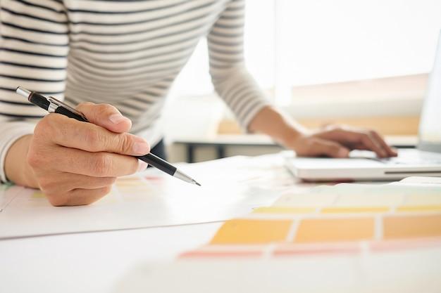 机の上にグラフィックデザインと色見本とペン。作業工具とアクセサリーを使用した建築図面