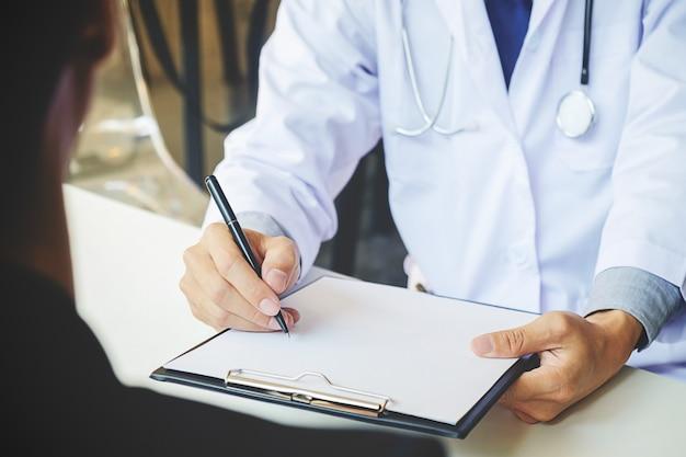 患者の症状を説明する男性の医師に熱心に耳を傾けたり、相談の中で書類を一緒に話し合って質問したりする患者