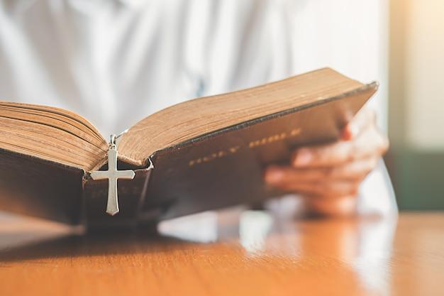 Христианская женщина молится о святой библии. руки, сложенные в молитве, святой библией в церкви