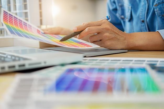 Графический дизайн и образцы цветов и ручки на столе.