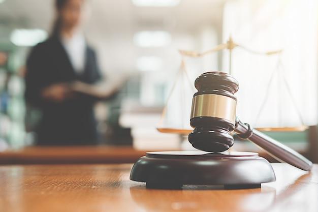 法律事務所の背景でチーム会議を持つ正義の弁護士と小槌を判断します。法と法務の概念