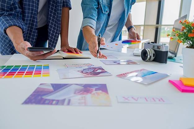 アジアの広告デザイナーの創造的なスタートアップチームがオフィスでアイデアを議論します。