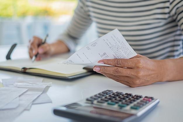 Женщина с векселями и калькулятором. женщина используя калькулятор для того чтобы высчитать счеты на таблице в офисе. расчет затрат.