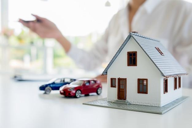 Модель автомобиля и дома с агентом и клиентом, обсуждающими контракт на покупку, получение страховки или ссуды на недвижимость или фон недвижимости.