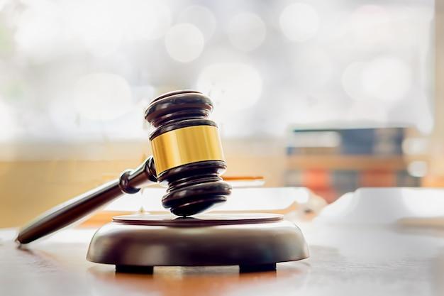 法律事務所の背景でチーム会議を持つ正義弁護士と小槌を判断します。法と法務の概念