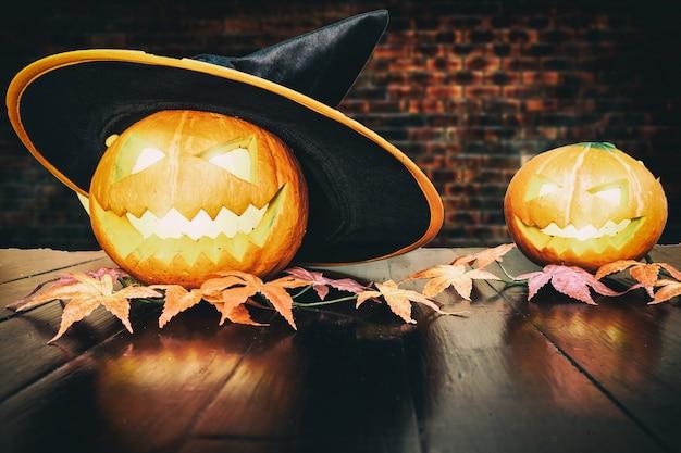 レンガの背景を持つ黒い木製テーブルの上のハロウィンかぼちゃ。ハロウィーンの休日の概念。
