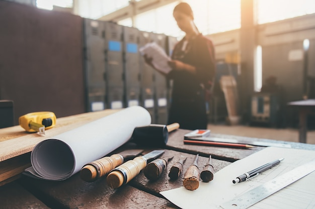 ワークショップのバックグラウンドで働く男と木製の機器。