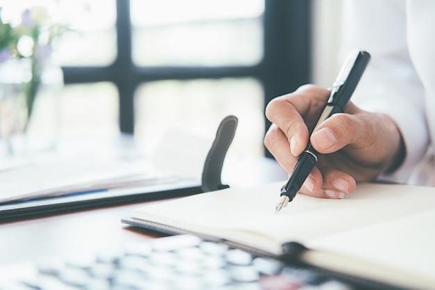 Женщина с векселями и калькулятором. женщина используя калькулятор для того чтобы высчитать счеты на таблице в офисе.