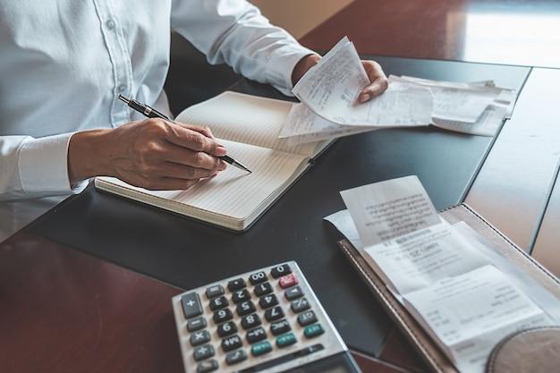 請求書と電卓を持つ女性。電卓を使用してオフィスのテーブルで請求書を計算する女性。