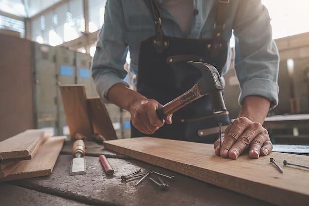 大工は大工仕事の木製テーブルの上の機器での作業します。