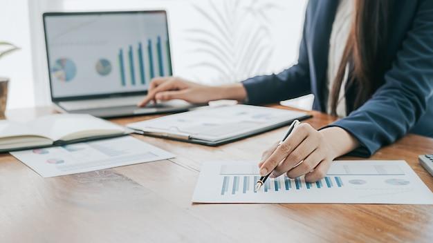 ビジネスコンセプトです。成功したチームワークの結果を示すチャートやグラフについて話し合うビジネスマン。