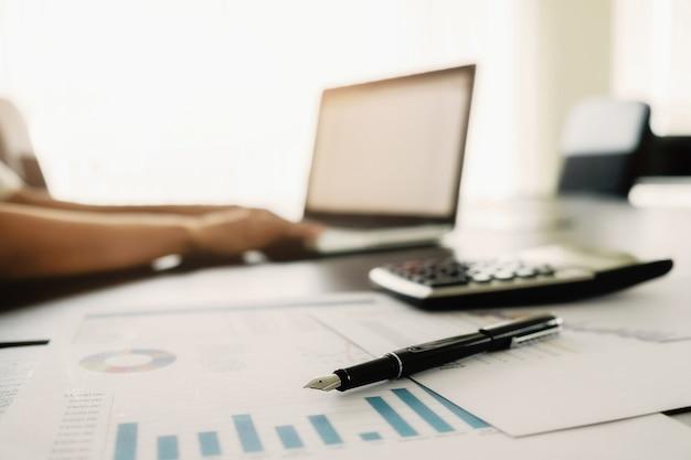 コピースペースとビジネスコンセプト。ペンフォーカスと分析チャート、コンピュータ、ノート、デスク上のコーヒーのカップでオフィスデスクテーブル。ヴィンテージトーンレトロフィルタ、選択フォーカス。