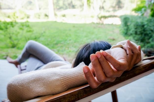 Красивая азиатская женщина, расслабляющий в саду