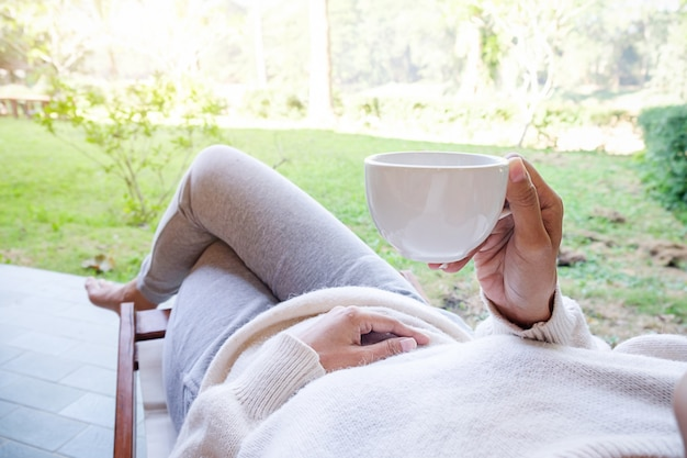 Красивая азиатская женщина в саду с чашкой кофе