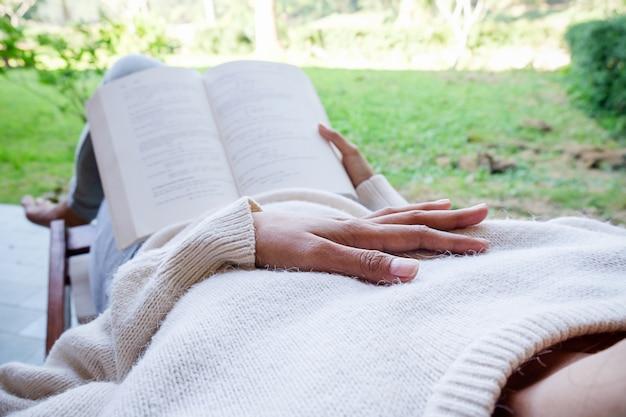 Красивая азиатская женщина в саду с книгой
