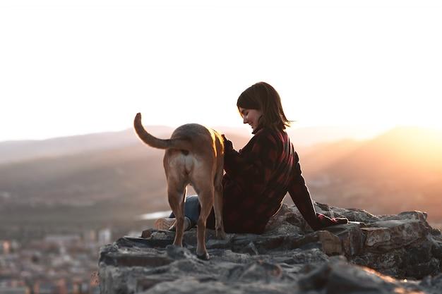 Девушка с ее собакой в скале с заходом солнца