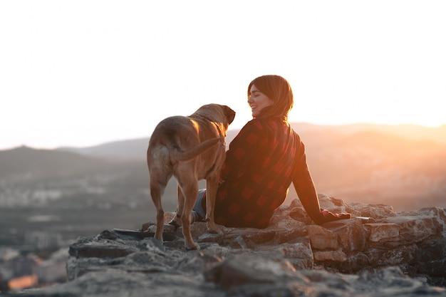 夕日と岩に彼女の犬を持つ少女