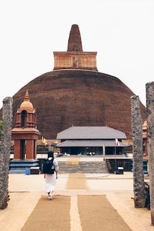 スリランカの茶色の仏教寺院に入る女の子