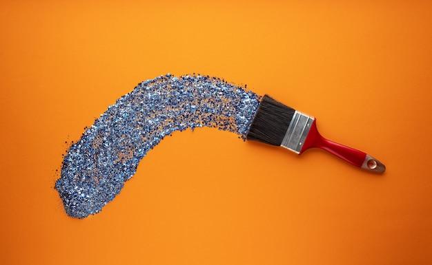 Кисть рисует мазок кисти с ярко-синим блеском на оранжевом фоне.