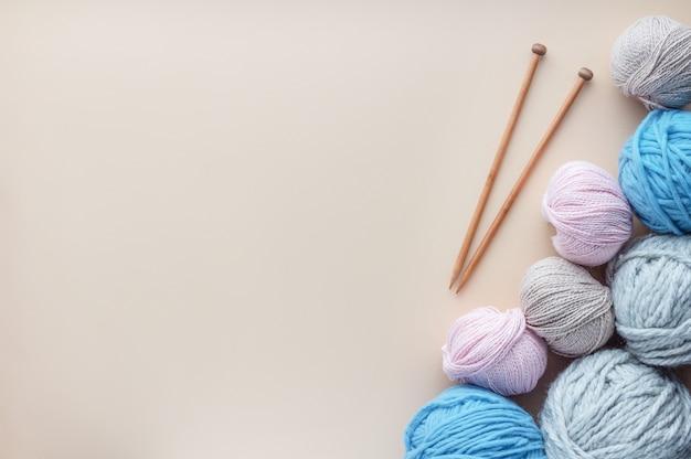 パステル調の背景に糸の束の近くに横になっている編み針。