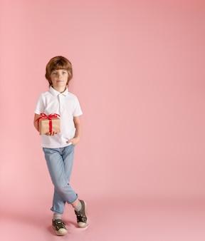 かわいい男の子はピンクの背景に彼の手で贈り物を保持しています。