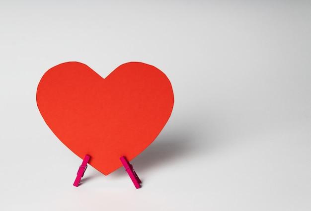 白い背景の上の木製洗濯はさみの上に紙の心が立っています。最小限の愛の概念。