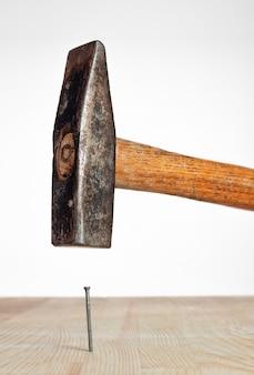 木の板に打たれたハンマーの釘
