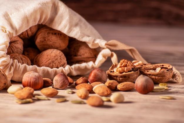 アーモンドナッツ、ヘーゼルナッツ、クルミ、木製のテーブルの黄麻布の袋に甘い種子