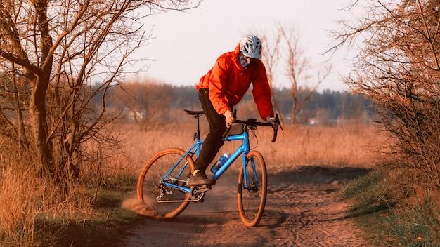 砂利自転車のサイクリストが道路に沿って走り、日没時に後輪からほこりを発生させます。砂利バイク。エクストリームスポーツとアクティビティのコンセプト。