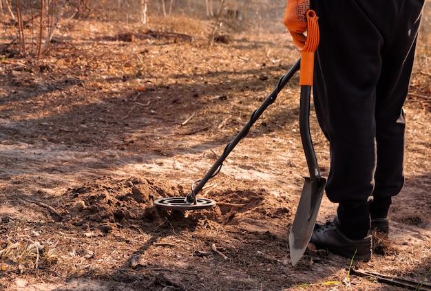 Человек с металлоискателем и лопатой ищет клад в лесу.