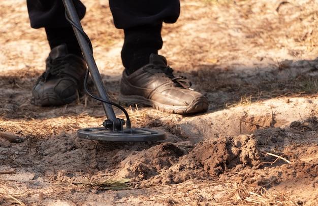 Мужчина ищет клад с металлоискателем в лесу.