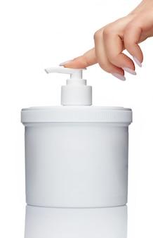 ディスペンサー付きボトル。石鹸、ジェル、防腐剤、化粧品の容器。女性の手がボトルのバルブを押します。白い背景で隔離されました。