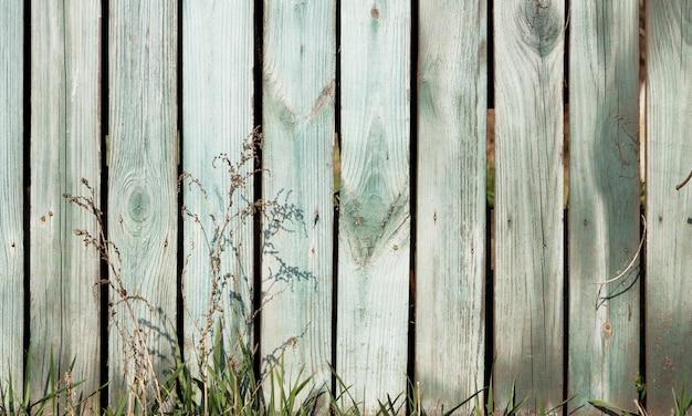 古い素朴なスタイルのフェンスの背景に緑の芝生。