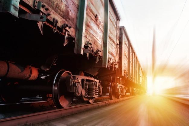夕暮れ時に通過する貨物列車。夕日の光の下で貨物を運ぶ列車。