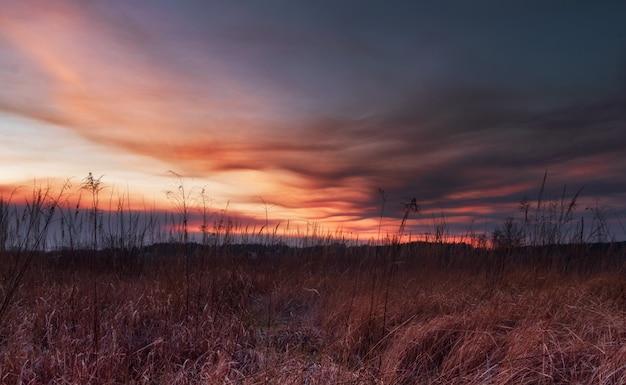 フィールドに沈む夕日。曇り空に沈む夕日。自然の中で美しい風景。