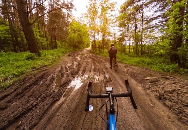 Два велосипедиста на гравийных велосипедах в лесу на грунтовой дороге с лужами