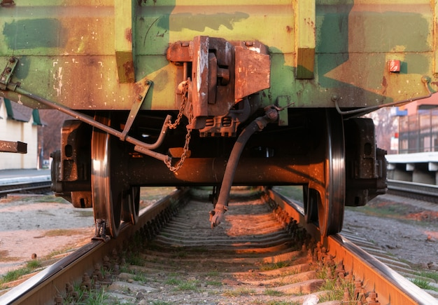 Вид сзади последнего вагона грузового поезда на железнодорожной станции на закате