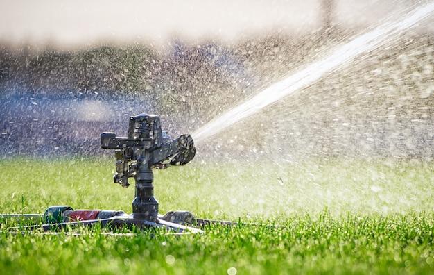 芝生に水をまく自動スプリンクラーシステム。閉じる