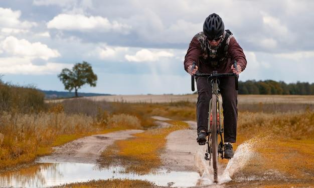 Горный байкер едет на гравийном велосипеде по грязной луже, оставляя брызги воды в поле