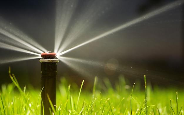 芝生に水をまく自動スプリンクラーシステム