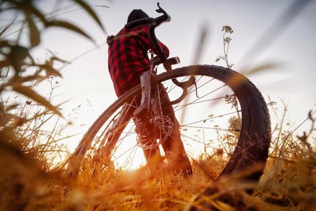 フィールドで自転車を持つ男。芝生のフィールドで日の出で彼の自転車に座っているサイクリストの広角ビュー。アクティブなライフスタイルのコンセプト。