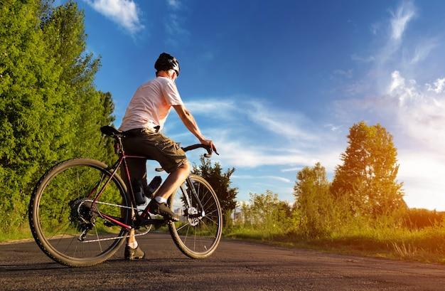 サイクリストは夕暮れ時の道に立っています。青空を背景にロードバイクを持つ男の美しい風景。スポーツライフスタイル。