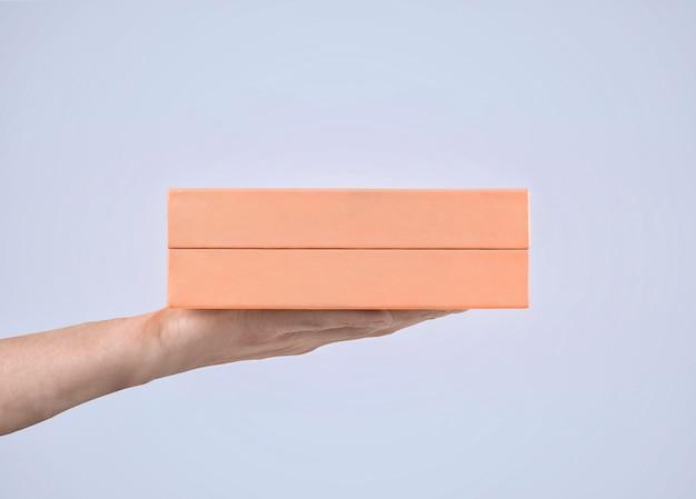 マンの手にピンクのギフトボックス。パステルカラー。