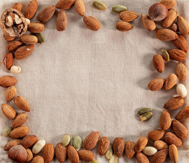 黄麻布の背景に異なるナッツのセット。
