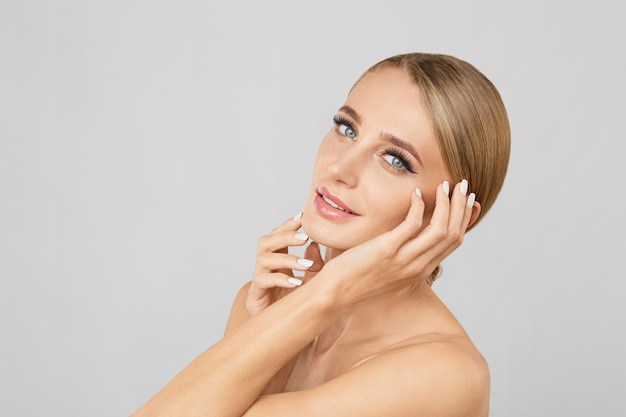 彼女の顔に触れる自然なメイクアップと笑顔の美しい金髪の女性の肖像画。