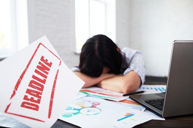 頭痛で疲れて邪魔女性労働者。オフィスで手に頭を抱え、締め切りを考えるストレス女性