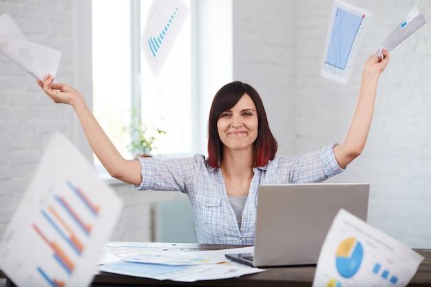 幸せと笑顔の女性労働者は、書類を落下してオフィスでドキュメントをスローします。時間内に作業を終了します。