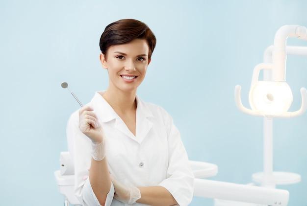 歯科医のオフィスで若い女性医師。歯科用ミラーを保持している白衣で笑顔美人。歯科医院。口腔病学